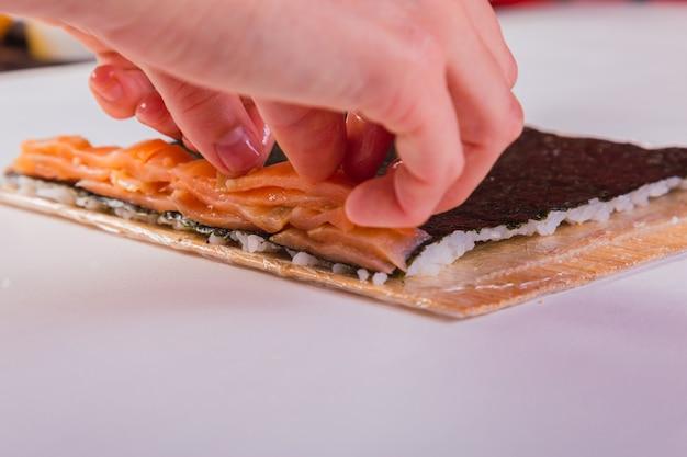 Primo piano delle mani di uno chef che preparano il sushi.