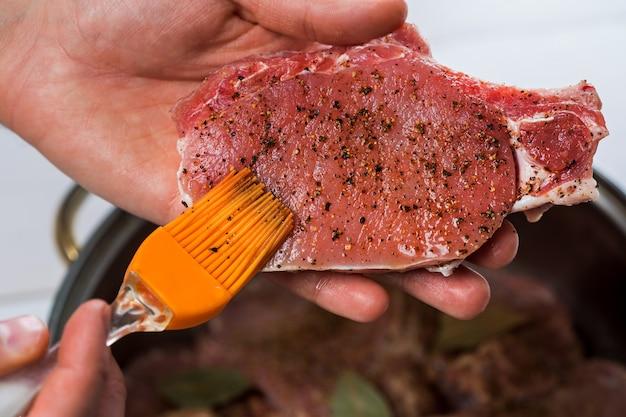 Chiuda in su delle mani dello chef speziando la carne. casseruola con carne cruda su sfondo bianco.