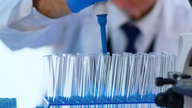 Primo piano della provetta di riempimento del chimico con liquido utilizzando una pipetta in un laboratorio attrezzato. scienziato che analizza vari batteri, tessuti e campioni di sangue, ricerca farmaceutica per antibiotici