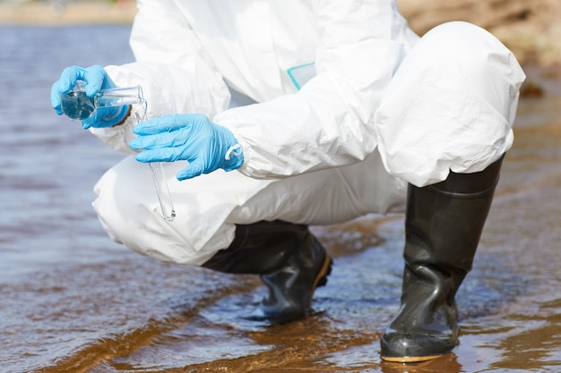 Primo piano del chimico in indumenti da lavoro protettivi e guanti che tengono la boccetta ed esaminano l'acqua nel fiume