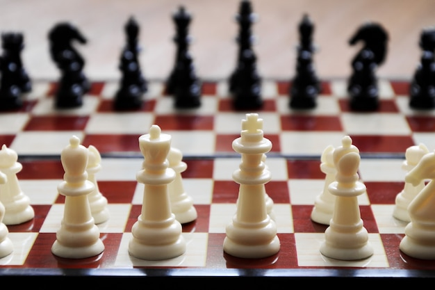 Primo piano dei pezzi degli scacchi posti sulla scacchiera all'inizio del gioco