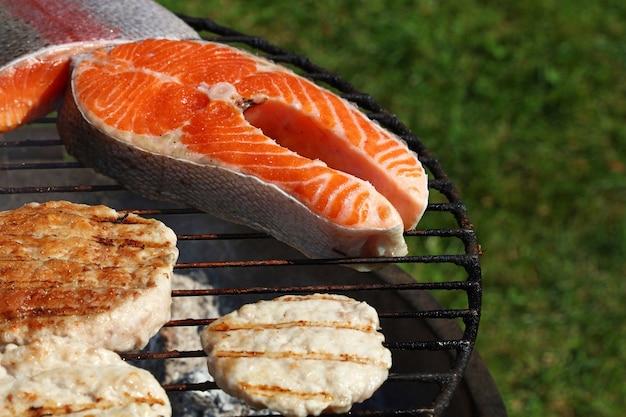 Primo piano hamburger di carne di pollo o tacchino per hamburger e bistecca di salmone preparata su una griglia per barbecue all'aperto, vista dall'alto