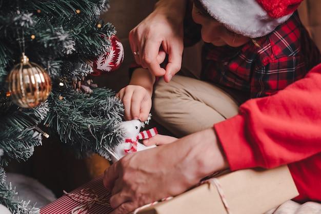Primo piano delle mani del padre e del bambino che appendono il giocattolo decorativo sul ramo dell'albero di natale