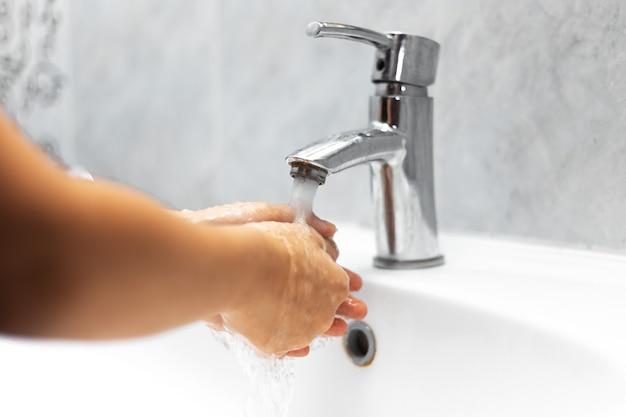 Primo piano della ragazza del bambino, lavandosi le mani sotto il rubinetto dell'acqua nel lavandino bianco
