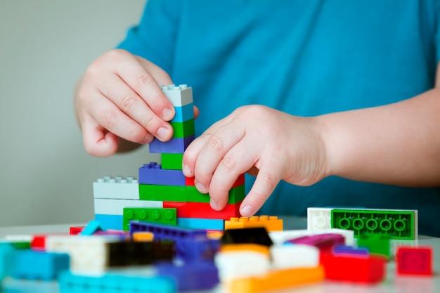 Chiuda in su delle mani del bambino che gioca con i mattoni di plastica colorati al tavolo.