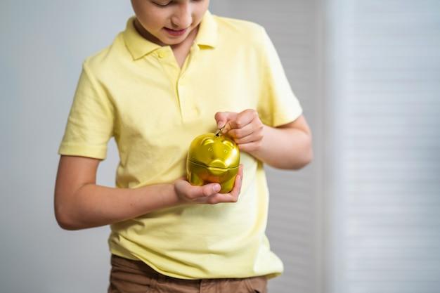 Primo piano di un bambino che mette le monete in un porcellino salvadanaio