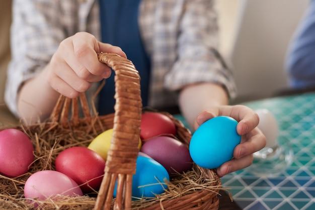 Primo piano del bambino che mette le uova colorate nel cestino e si prepara per le vacanze di pasqua