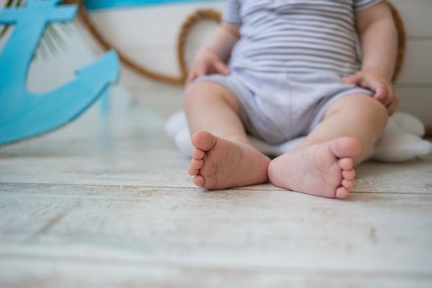 Primo piano dei piedi nudi di un bambino su un pavimento di legno con spazio per il testo