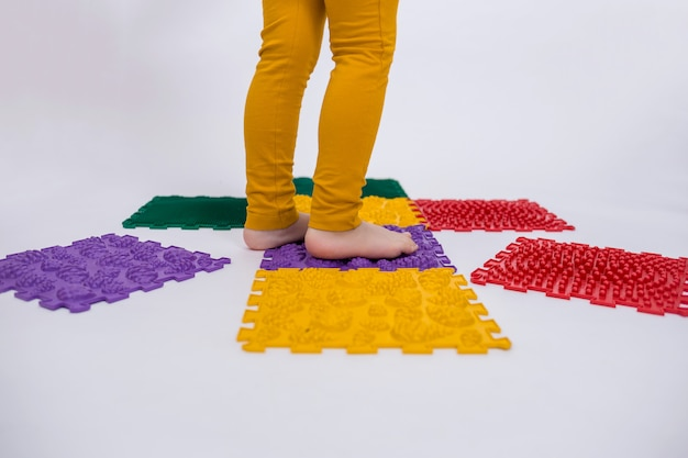 Primo piano dei piedi di un bambino che cammina su una stuoia ortopedica su uno sfondo bianco isolato con spazio per il testo. prevenzione dei piedi piatti