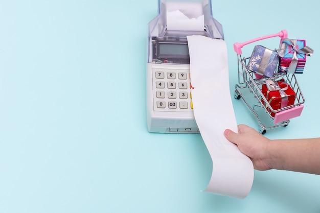 Primo piano della mano di un bambino che tiene una ricevuta del cassiere in bianco sopra il registratore di cassa accanto a un carrello della spesa con scatole regalo avvolte