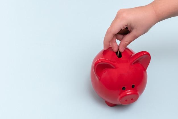 Primo piano della mano di un bambino mette una moneta in un salvadanaio rosso