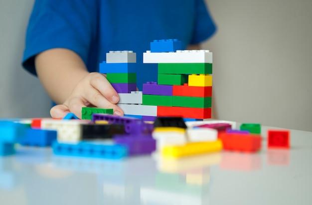 Chiuda in su delle mani del bambino che gioca con i mattoni di plastica colorati al tavolo. bambino che si diverte e costruisce con mattoni luminosi del costruttore. apprendimento precoce. sfondo a strisce. sviluppo di giocattoli.