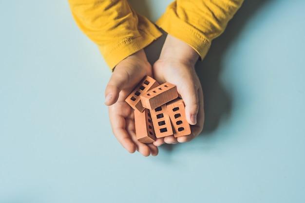 Chiuda in su delle mani del bambino che gioca con i piccoli mattoni di argilla reale al tavolo