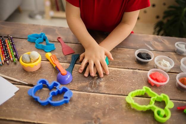Primo piano delle mani di un bambino che scolpiscono dall'argilla su un tavolo in legno con accessori per la creatività