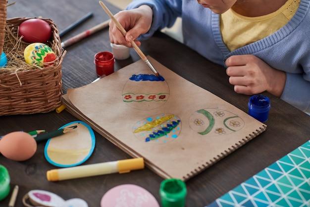 Primo piano del bambino seduto al tavolo e che dipinge le uova su carta per le vacanze di pasqua