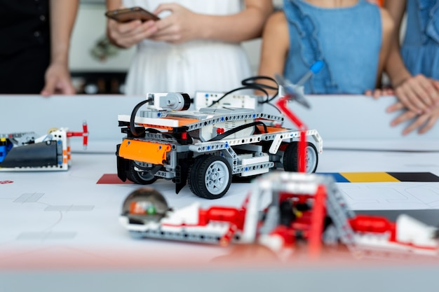 I bambini in primo piano controllano i robot delle automobili assemblati da un costruttore programmato su un computer in una scuola di robotica