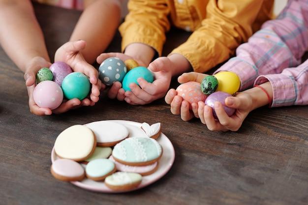Primo piano di bambini che tengono le uova di pasqua in mano seduti al tavolo di legno con un piatto con biscotti fatti in casa