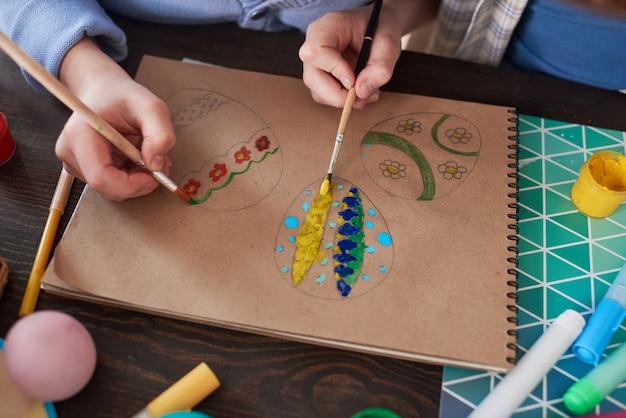 Primo piano di bambini che dipingono le uova di pasqua su carta con pennelli a tavola durante le lezioni d'arte