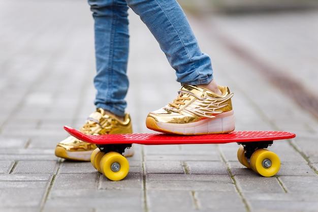 Chiudere i piedi del bambino in scarpe da ginnastica su uno skateboard