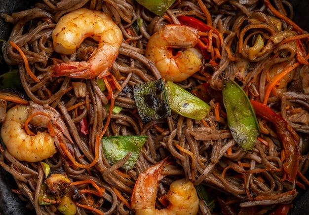 Primo piano di spaghetti saltati in padella di soba cinese con gamberi e verdure, carota, fagiolini, funghi, pepe, vista dall'alto. pasto asiatico tradizionale