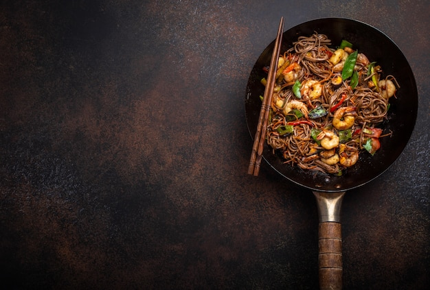 Primo piano di spaghetti saltati in padella di soba cinesi con gamberetti, verdure in una vecchia padella wok rustica servita su sfondo di cemento, primo piano, vista dall'alto. piatto tradizionale asiatico/thai, spazio per il testo