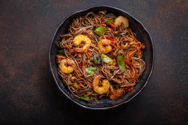 Primo piano di spaghetti saltati in padella di soba cinesi con gamberetti, verdure in padella in ceramica rustica servita su sfondo di cemento, primo piano, vista dall'alto. piatto tradizionale asiatico/thai, pasto in stile cinese Foto Premium