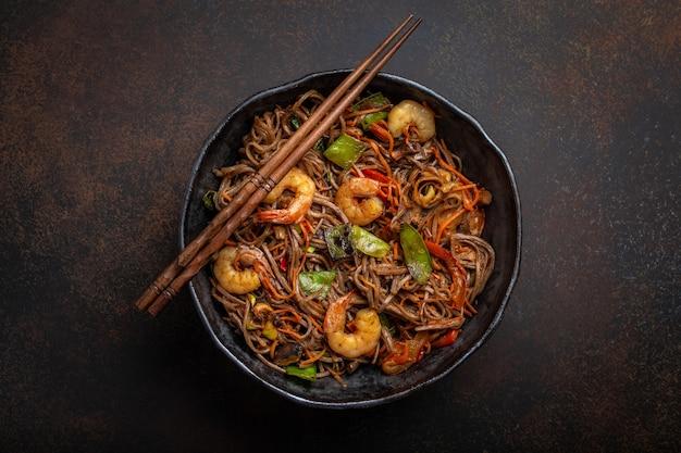 Primo piano di spaghetti saltati in padella di soba cinesi con gamberetti, verdure in padella in ceramica rustica servita su sfondo di cemento, primo piano, vista dall'alto. piatto tradizionale asiatico/thai, pasto in stile cinese