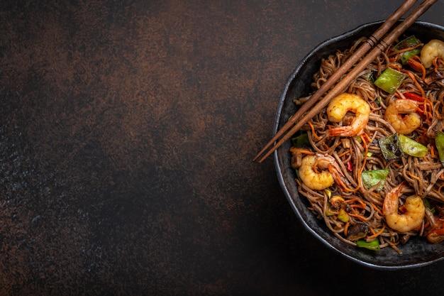 Primo piano di spaghetti saltati in padella di soba cinesi con gamberetti, verdure in padella in ceramica rustica servita su sfondo di cemento, primo piano, vista dall'alto. piatto tradizionale asiatico/thai, spazio per il testo Foto Premium