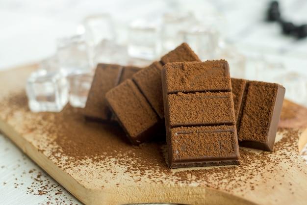 Chiuda in su una barra di cioccolato e cubetti di ghiaccio sul piatto di legno