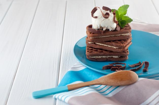 Primo piano di biscotti al cioccolato ricoperti di pallina di gelato alla vaniglia con copyspace