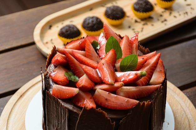Close up di torta al cioccolato ricoperta di fragole, foglie di basilico, marmellata di more e con intorno piatti di cioccolato. in sottofondo il brigadiere (dolce brasiliano).