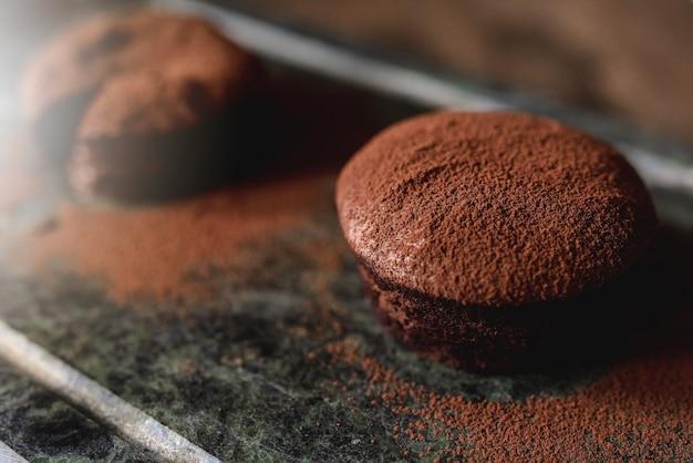 Primo piano di torta al cioccolato con cuore fondente e cacao in polvere come decorazione per il dessert.