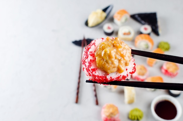 Close up di bacchette prendendo porzione di sushi roll sopra la tavola con un assortimento di sushi, salsa di soia,