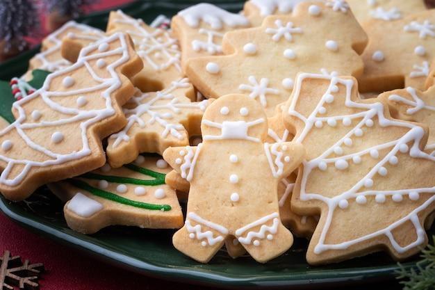 Close up di natale decorato zucchero cooikes in un piatto sul tavolo rosso sullo sfondo.