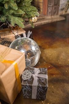 Primo piano di un albero di natale decorato con palline d'oro. sotto l'albero di natale un gran numero di