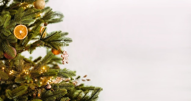 Primo piano di un albero di natale con i giocattoli delle decorazioni, arancia secca su una priorità bassa bianca.