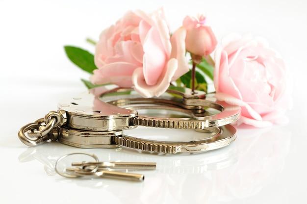 Le manette e le chiavi cromate del primo piano si trovano su un tavolo bianco accanto a due fiori rosa. concetto di schiavitù volontaria concetto giochi bdsm.