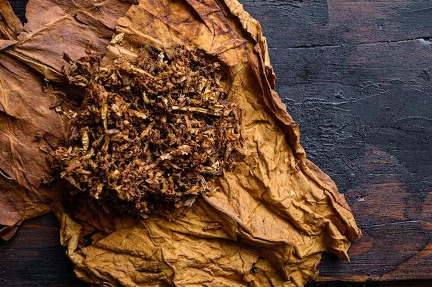 Primo piano del sigaro e del mucchio di tabacco su legno