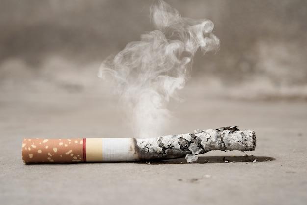 Chiuda sulla bruciatura della sigaretta sul pavimento di calcestruzzo, smetta di smettere di fumare il concetto