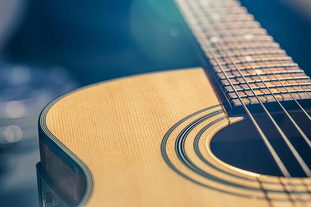 Primo piano di una chitarra acustica classica su uno sfondo sfocato con bokeh.