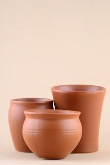 Primo piano dei vasi di argilla sulla parete color crema