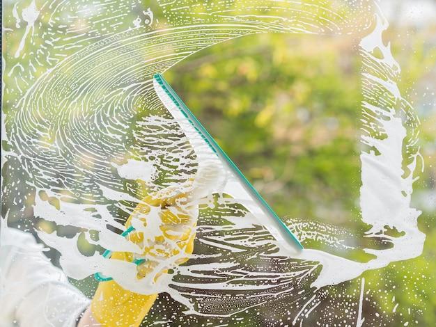 Pulitore del primo piano che lava la finestra