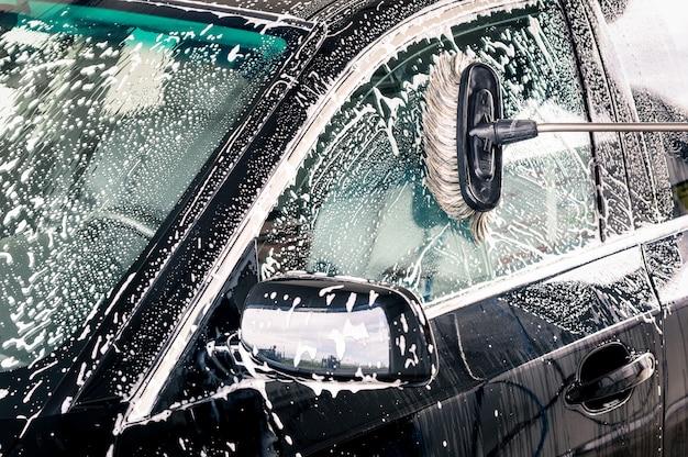 Chiuda in su della spazzola di pulizia sull'automobile