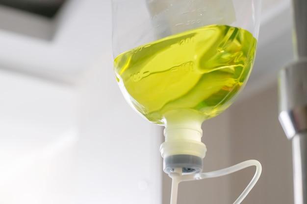Primo piano di una bottiglia di soluzione salina verde trasparente appesa a un supporto per l'uso con un paziente.