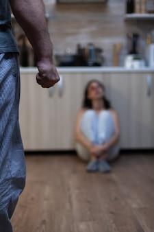 Primo piano del pugno chiuso dell'uomo aggressivo dopo aver abusato della donna