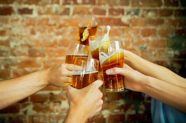 Tintinnare in primo piano. giovane gruppo di amici che bevono birra, si divertono, ridono e festeggiano insieme. donne e uomini con bicchieri di birra. oktoberfest, amicizia, solidarietà, concetto di felicità.