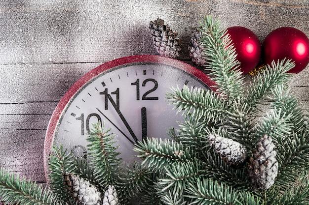 Primo piano dell'orologio con il fondo dell'albero di natale della neve