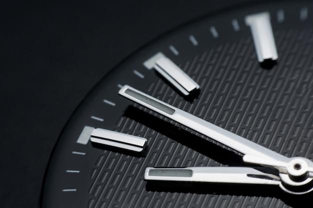 Chiuda in senso orario sul fondo nero dell'orologio. orologio da polso in stile retrò