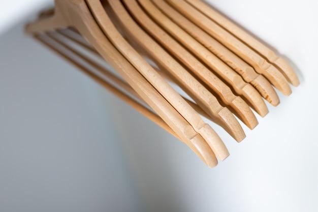 Close up di stoffa appendiabiti in legno in fila sul muro bianco. appendiabiti nell'armadio.
