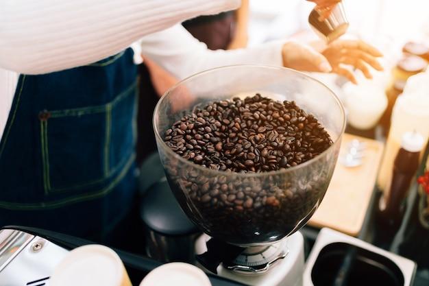 Chicchi di caffè del primo piano all'interno della macchina per la frantumazione elettrica della smerigliatrice di caffè.